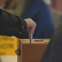 Une main déposant son vote dans la boîte.