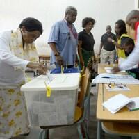 Des femmes et des hommes dans un bureau de vote