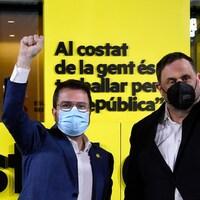 Deux hommes, dont un portant des lunettes, posent le visage couvert d'un masque, le poing levé en signe de victoire.