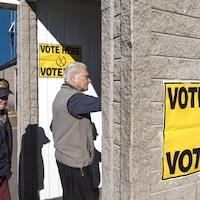 Deux hommes entrent dans un bâtiment sur lequel il est écrit : « Vote here, votez ici ».
