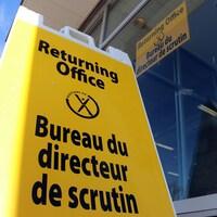 Une affiche jaune posée sur le trottoir indique qu'il s'agit du bureau du directeur de scrutin.