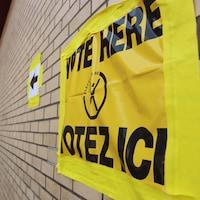 Une affiche jaune sur un mur indique la direction du bureau de vote.