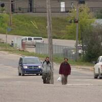 Deux hommes marchent sur le trottoir avec des véhicules en fond d'écran.