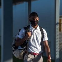 Un élève du secondaire se rend à l'école avec un masque.