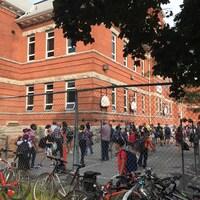 Des dizaines d'élèves sont présents dans la cour d'école.