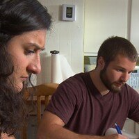 Le frère et la soeur font leurs travaux universitaires sur la table de la cuisine.