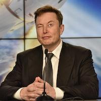 Elon Musk livre une conférence assis à une table avec un microphone devant lui. Il a un oeil fermé et un oeil ouvert.