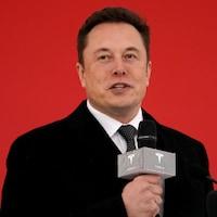 Elon Musk parle au micro devant un mur rouge.
