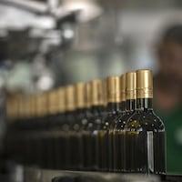 Une rangée de bouteilles de vin blanc sur une chaîne de montage, en train d'être étiquettées