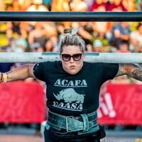 Une femme soulève une structure en acier sur ses épaules lors d'une compétition.