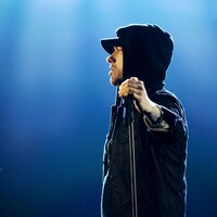Eminem porte un vêtement à capuche et tient un micro dans la main droite.