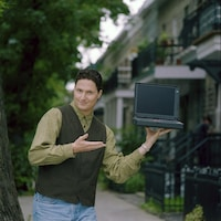Jean-Hugues Roy qui présente un ordinateur portable qu'il tient d'une main.