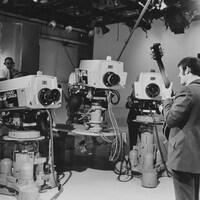 Trois caméras devant le guitariste Éric Nico, dans le studio de l'émission Zoom.