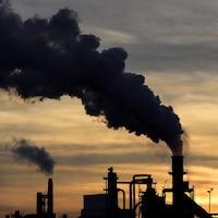 Une colonne de fumée noire s'échappe de la cheminée d'un complexe industriel.