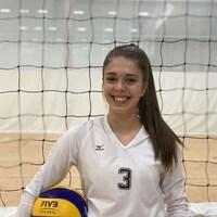 Emma sourit devant un filet dans un gymnase en tenant un ballon de volley-ball dans son bras droit.