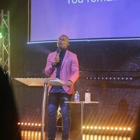 Emmanuel Adewusi est sur scène. Il a les yeux fermés et parle dans un micro.