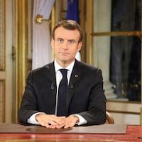 Emmanuel Macron est assis derrière un bureau à l'Élysée lors de son discours.
