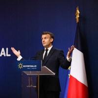 Bras ouverts, Emmanuel Macron se tient derrière un lutrin.