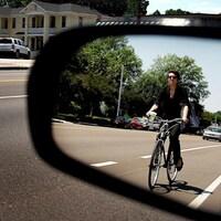 Un automobiliste voit une cycliste dans son rétroviseur extérieur.