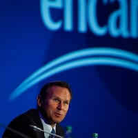 Le président d'Encana, Doug Suttles, devant un écran géant où figure le logo de l'entreprise.