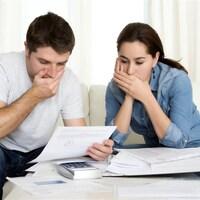 Un couple choqué devant leurs factures.