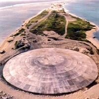 Un vaste dôme circulaire de béton trône sur une petite île verte encerclée d'eau bleue.