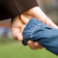 Photo d'un adulte qui tient la main d'un enfant.