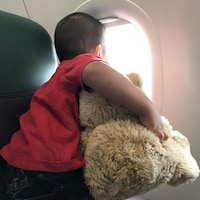 Un garçon qui tient un ourson regarde par un hublot d'avion.