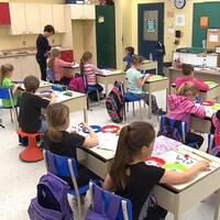 Une vingtaine de jeunes enfants assis dans une classe
