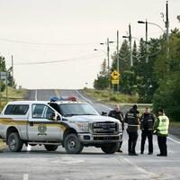 Une voiture de police stationnée au travers d'une route de campagne.  Quatre policiers discutent dehors.