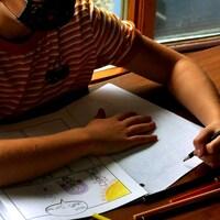 Un enfant avec un masque fait ses devoirs