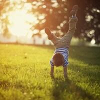 Un petit garçon se tient en équilibre sur les mains.