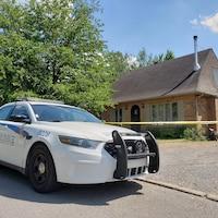 Une voiture de police devant une résidence autour de laquelle un ruban jaune du service de police a été installé.