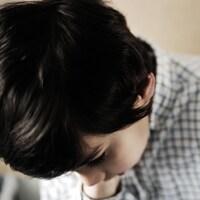 Une photo d'un jeune garçon posant son visage sur sa main.