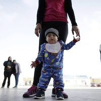 Un enfant et sa mère entourés par d'autres migrants.