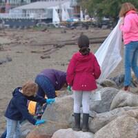 Quatre élèves de l'École Cousteau ramassent des déchets sur la plage.
