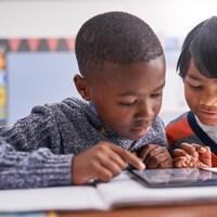 Deux jeunes garçons consultent une tablette dans une salle de cours.