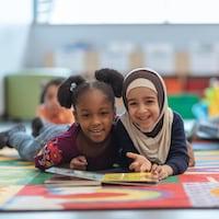 Deux fillettes allongées sur un tapis, dans une salle de classe, lisent un livre.