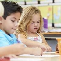 Quatre enfants dessinent à une table dans une garderie.