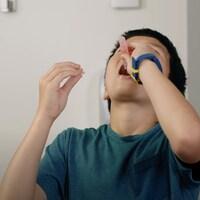 Arrêt sur image d'une vidéo explicative pour le nouveau test de dépistage gargarisant, où l'on voit un enfant vider un tube dans sa bouche.