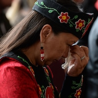 Une femme pleure la tête penchée et tente d'essuyer ses larmes avec un mouchoir blanc.