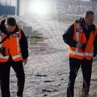 Deux hommes portant des vestes orange sur lesquelles on peut voir les lettres TSB et BST marchent sur un terrain extérieur, appareil photo en main.