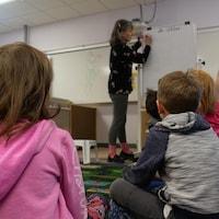Une enseignante enseigne aux enfants de la classe assis sur un tapis.
