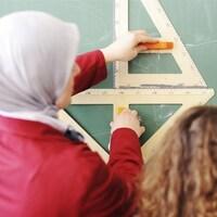 Une enseignante arborant un voile donne des explications à une élève.