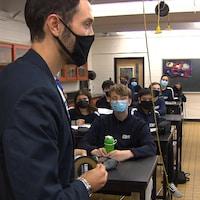Daniel Jacob, debout devant la classe et portant un masque, s'adresse aux élèves assis devant lui.