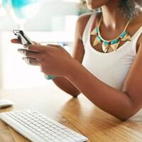 Une femme noire tient son portable, devant un ordinateur.