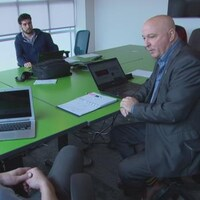 Trois hommes assis à une table de réunion
