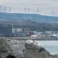 Une entreprise aux abords du fleuve Saint-Laurent. Des éoliennes surplombent l'entreprise.