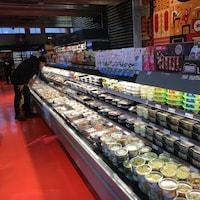 Un homme se tient devant des mets préparés dans une épicerie.