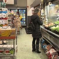 Une femme achète des légumes dans une épicerie.